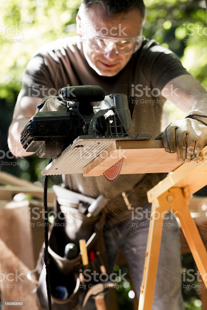 Male Carpenter Cutting Wooden Plank With Circular Saw. stock photo