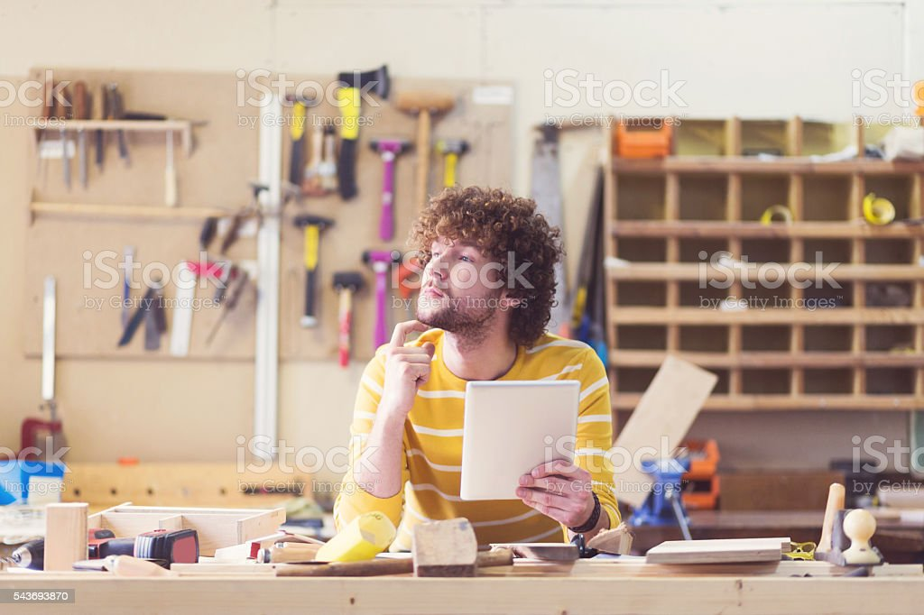 Male carpenter in a construction workshop stock photo
