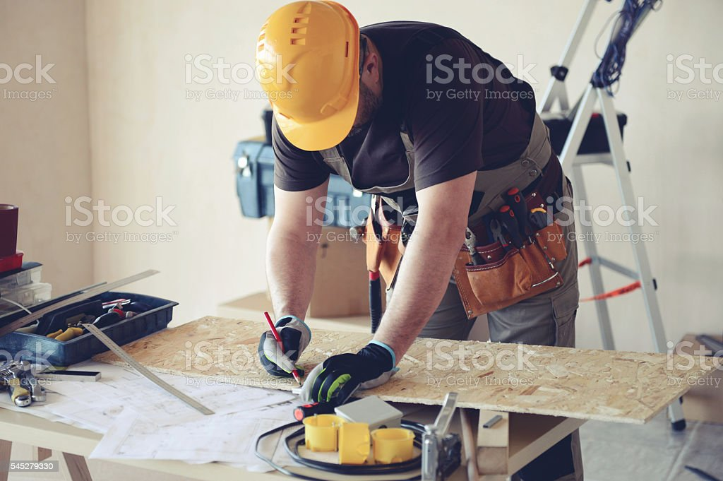 Male carpenter in working clothes in a construction workshop stock photo