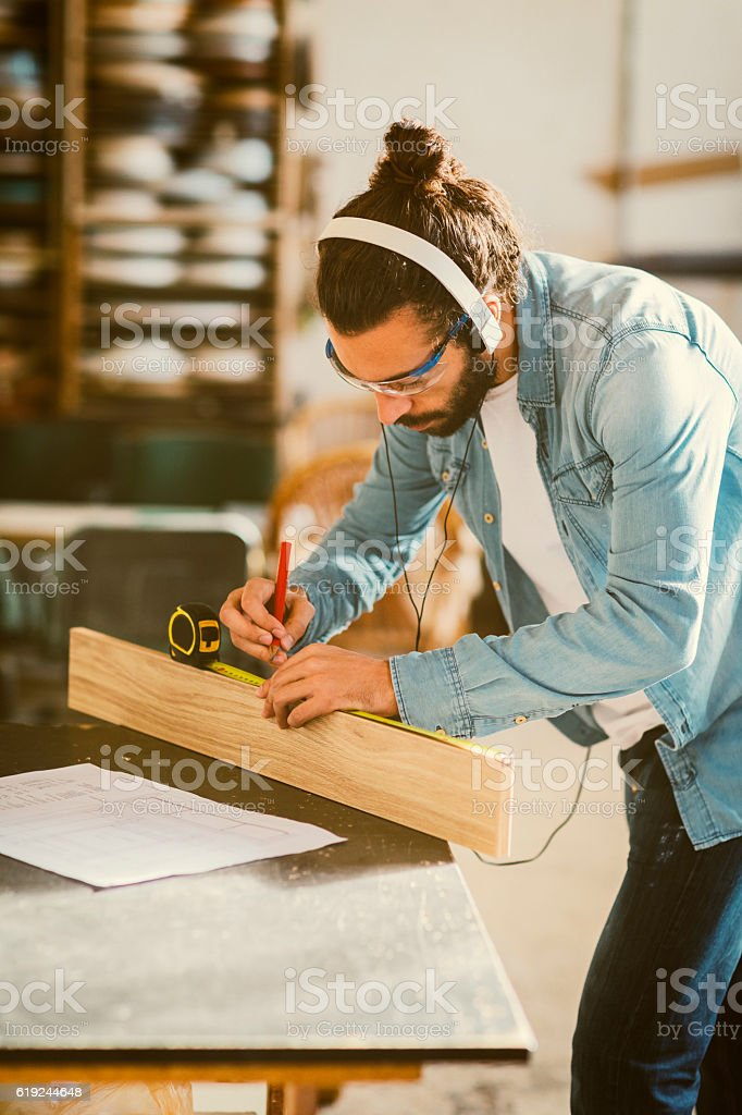 Male Carpenter Measuring Plank In His Workshop stock photo