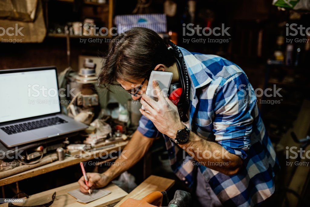 Male carpenter on phone and laptop at the workshop stock photo