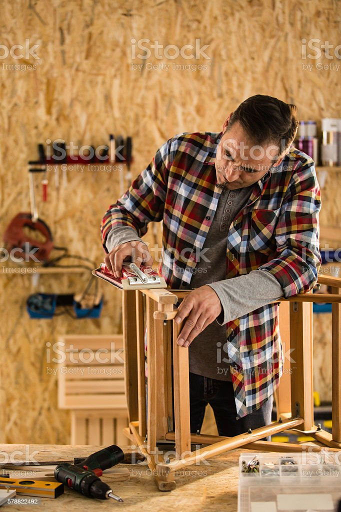 Male carpenter sanding wooden chair stock photo