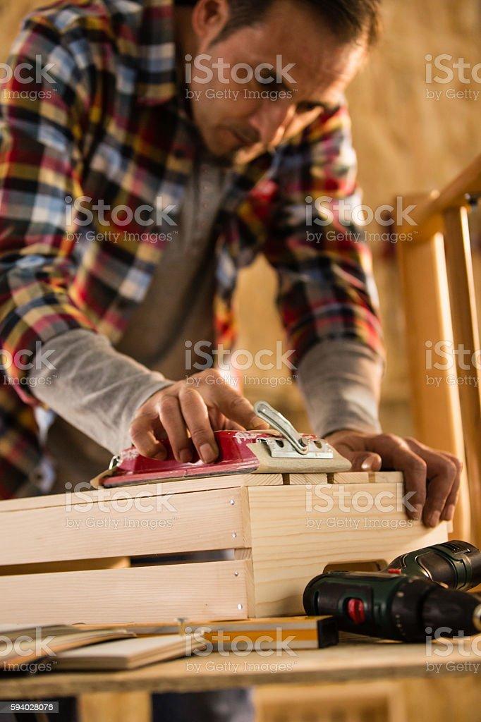 Male carpenter sanding wooden furniture stock photo