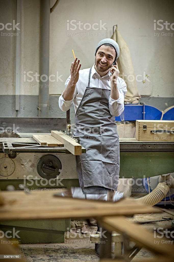 Male carpenter talking on the phone in the workshop stock photo