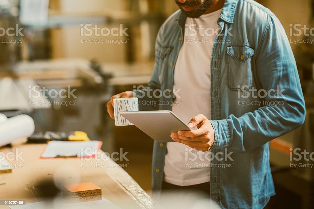 Male Carpenter Using Digital Tablet In His Workshop stock photo