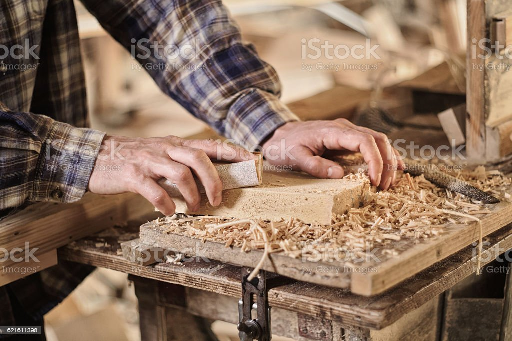 Male carpentry worker using sandpaper in workshop stock photo