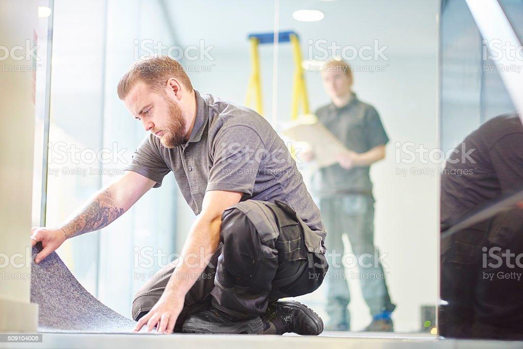 male carpet fitter fitting office carpet tiles stock photo