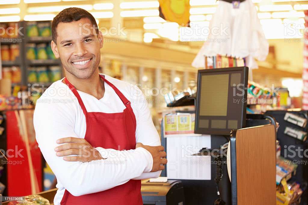 Male Cashier At Supermarket Checkout stock photo
