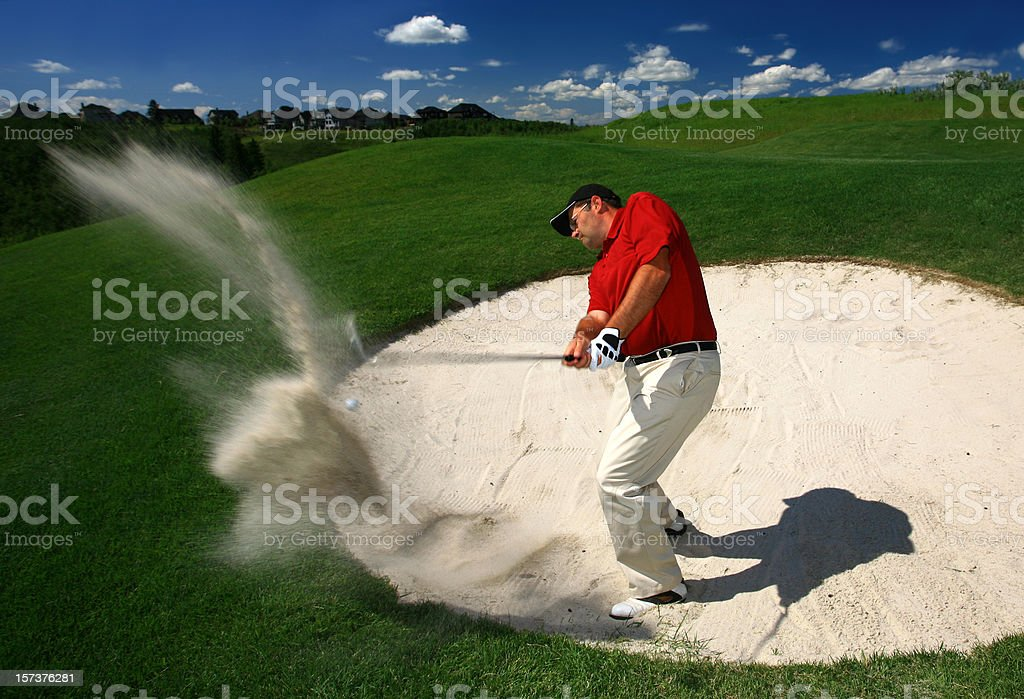 Male Caucasian Golfer Blasting Out of a Sand Trap stock photo