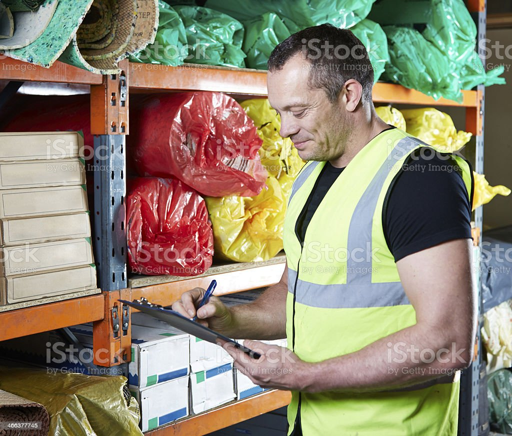 Male checking paperwork in warehouse stock photo