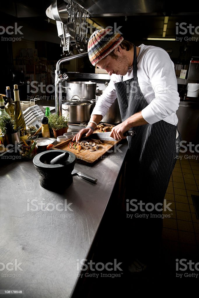 Male chef cutting vegetables on a restaurant kitchen counter royalty-free stock photo