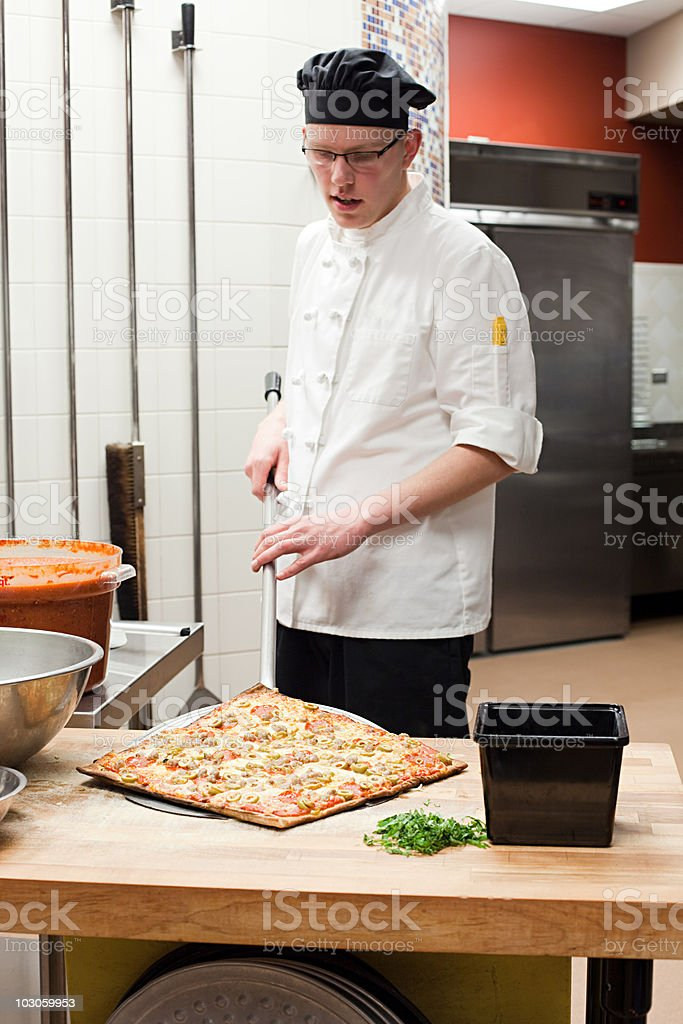Male chef making pizza in commercial kitchen stock photo
