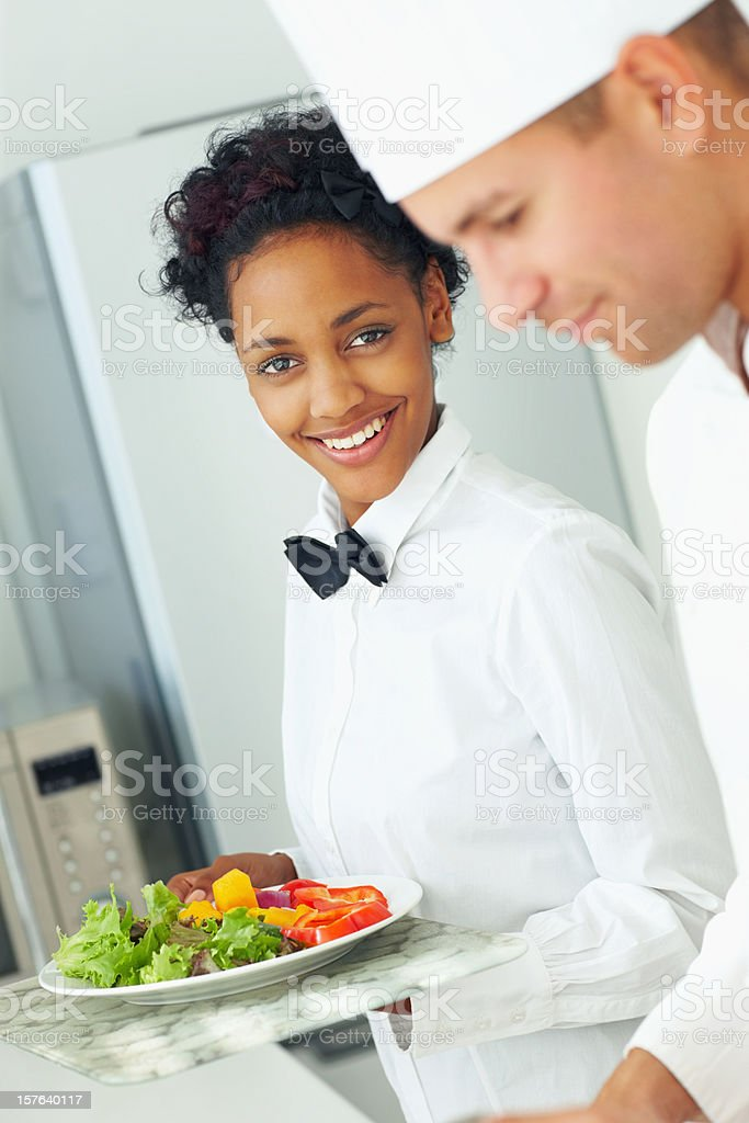 Male chef preparing food while a waitress holding fresh salad royalty-free stock photo