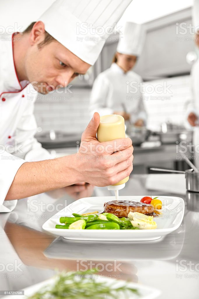 Male chef preparing steak plate stock photo