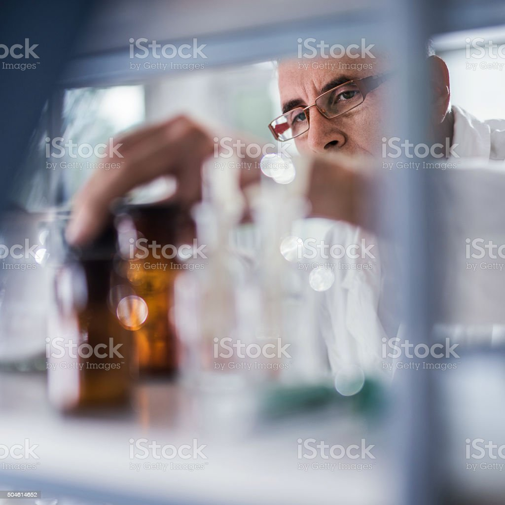 Male chemist choosing the right bottle for his scientific experiment. stock photo