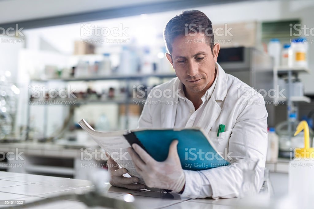 Male chemist reading medical data in laboratory. stock photo
