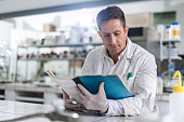 Male chemist reading medical data in laboratory.
