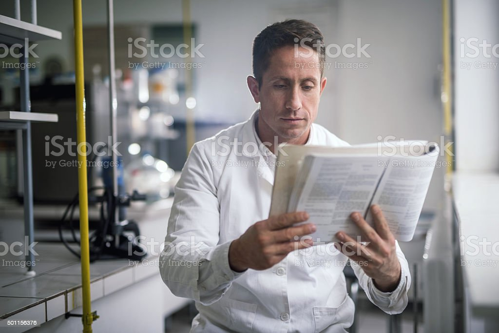 Male chemist reading scientific data from a book. stock photo