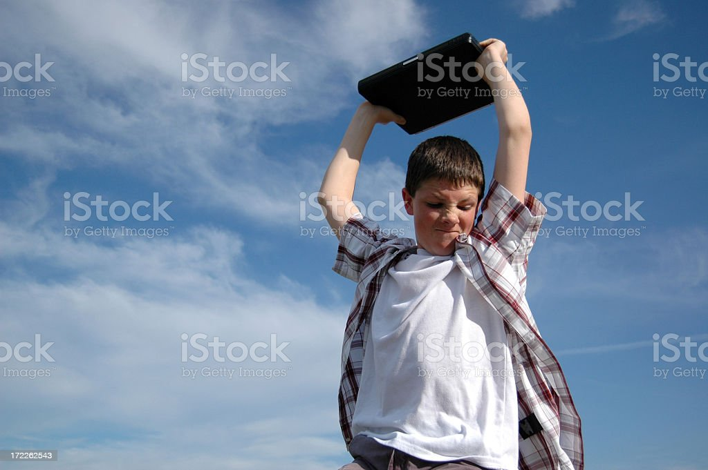 Male child frowning with laptop raised over his head royalty-free stock photo