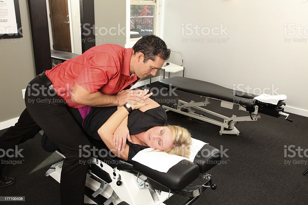 Male chiropractor assisting woman patient with her arm stock photo