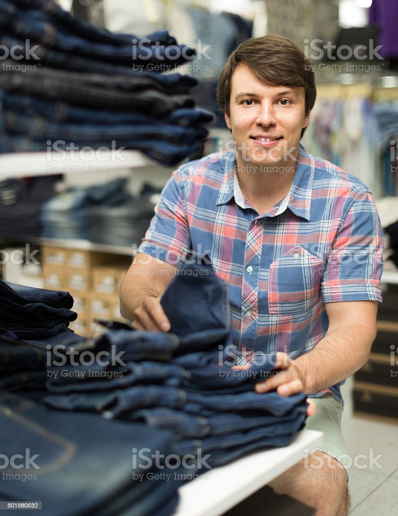 male chooses jeans at clothing store stock photo