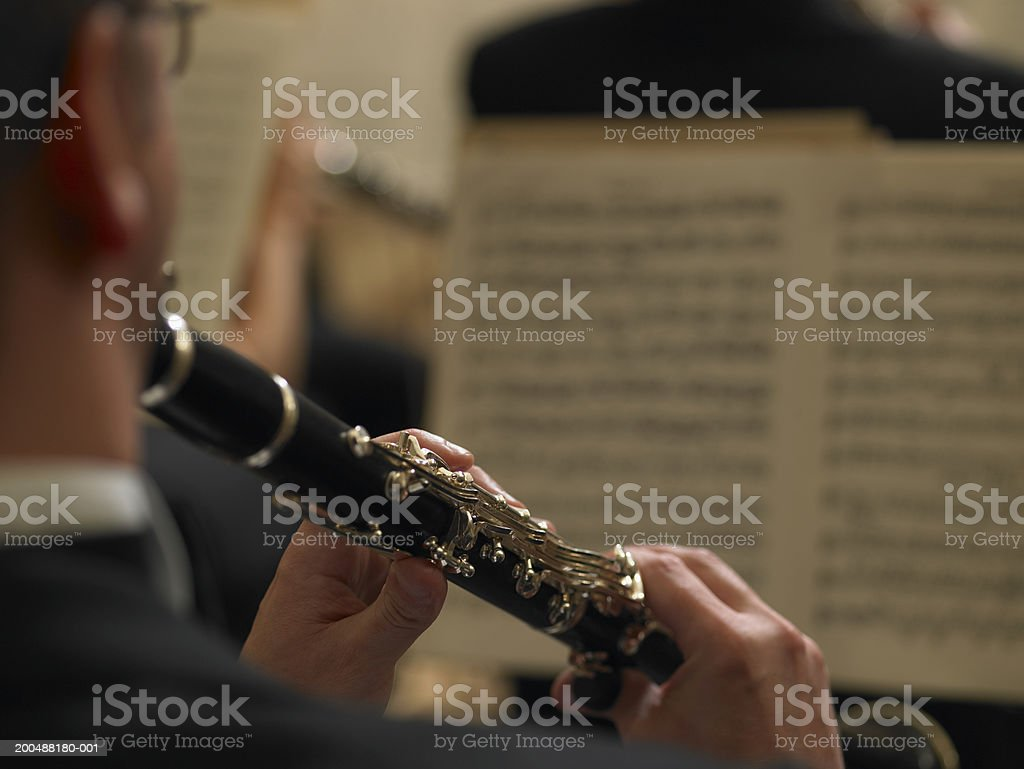 Male clarinetist performing in orchestra, close-up, rear view stock photo