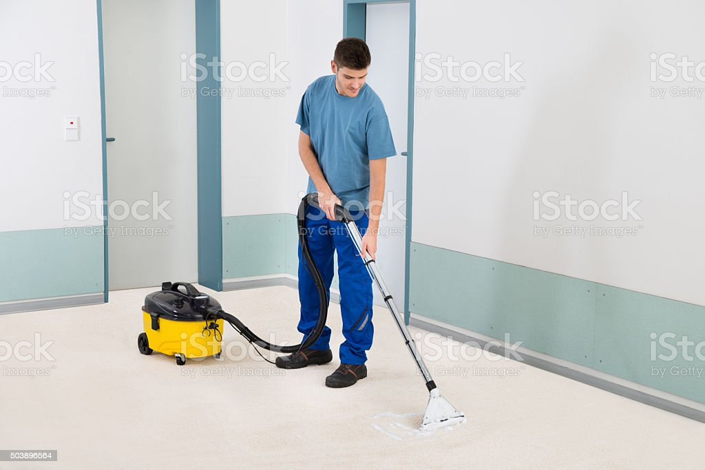 Male Cleaner Vacuuming Floor stock photo