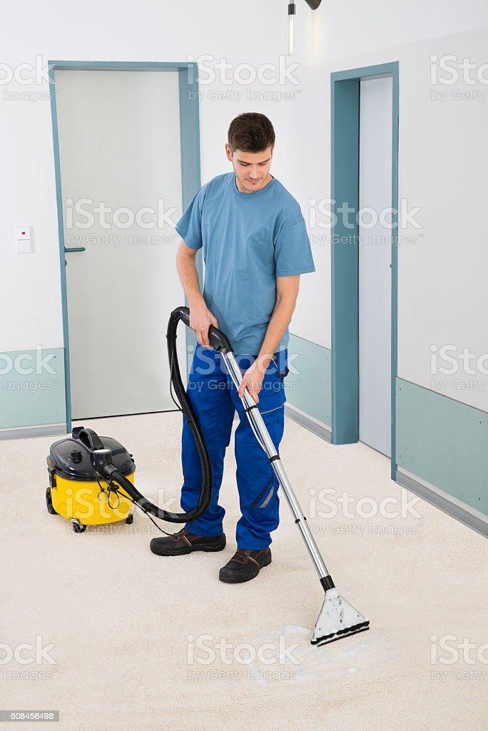 Male Cleaner Vacuuming Floor stock photo
