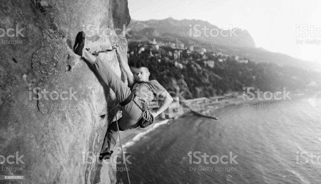 Male climber climbing big boulder in nature with rope stock photo