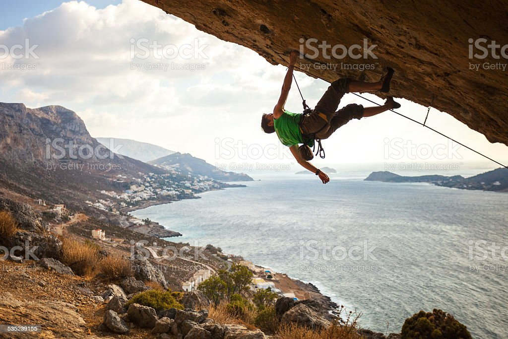 Male climber climbing overhanging rock stock photo