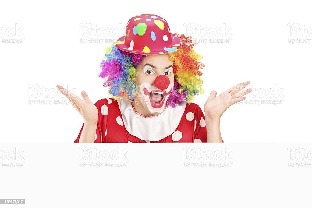 Male clown gesturing behind blank panel royalty-free stock photo
