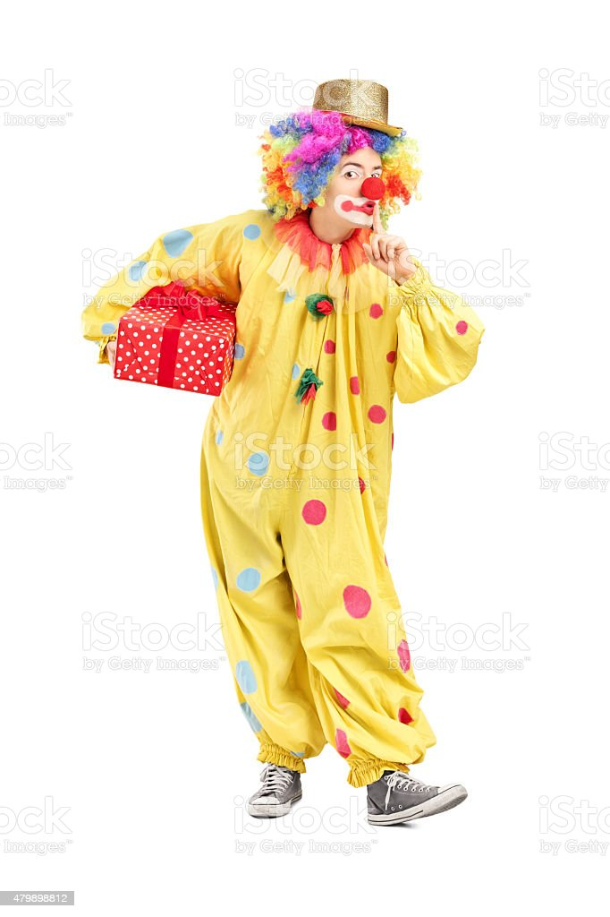 Male clown holding a present stock photo