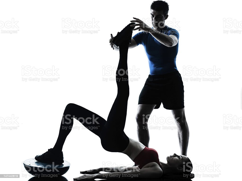 Male coach helping woman exercise abdominals using Bosu stock photo