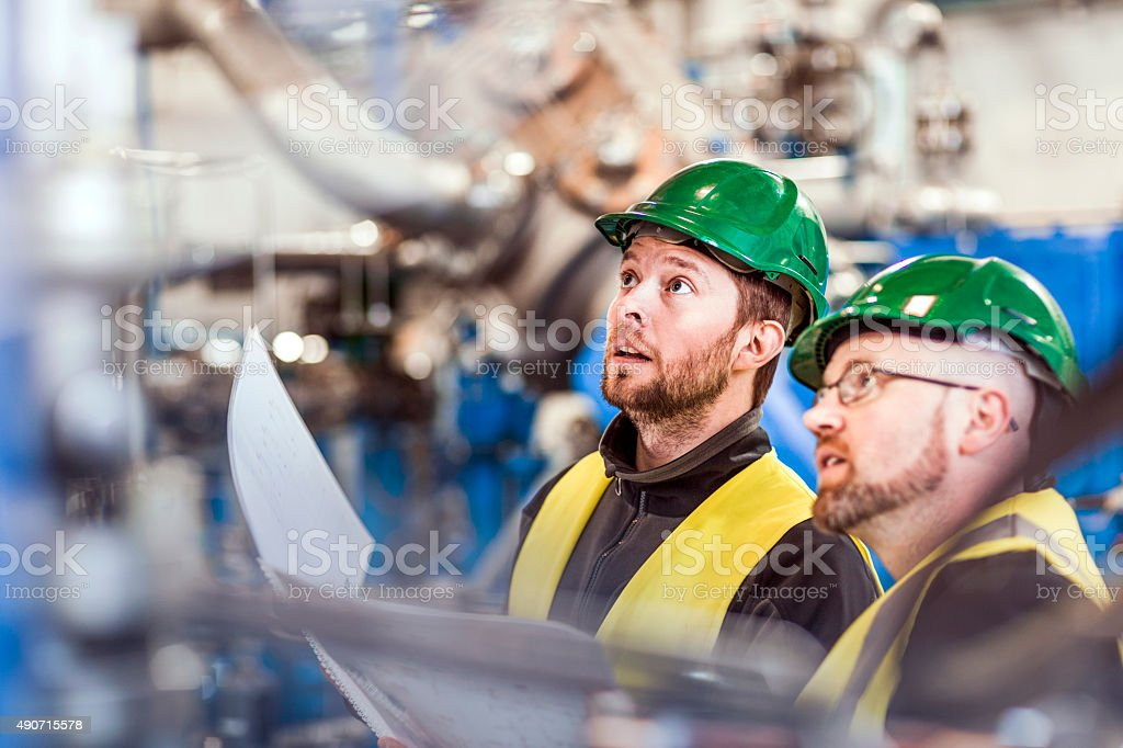 Male colleagues analysing machine in industry stock photo