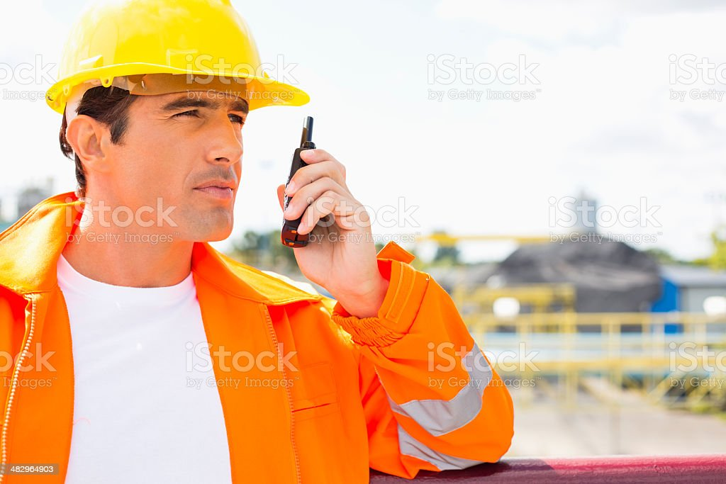 Male construction worker communicating on walkie-talkie at site stock photo