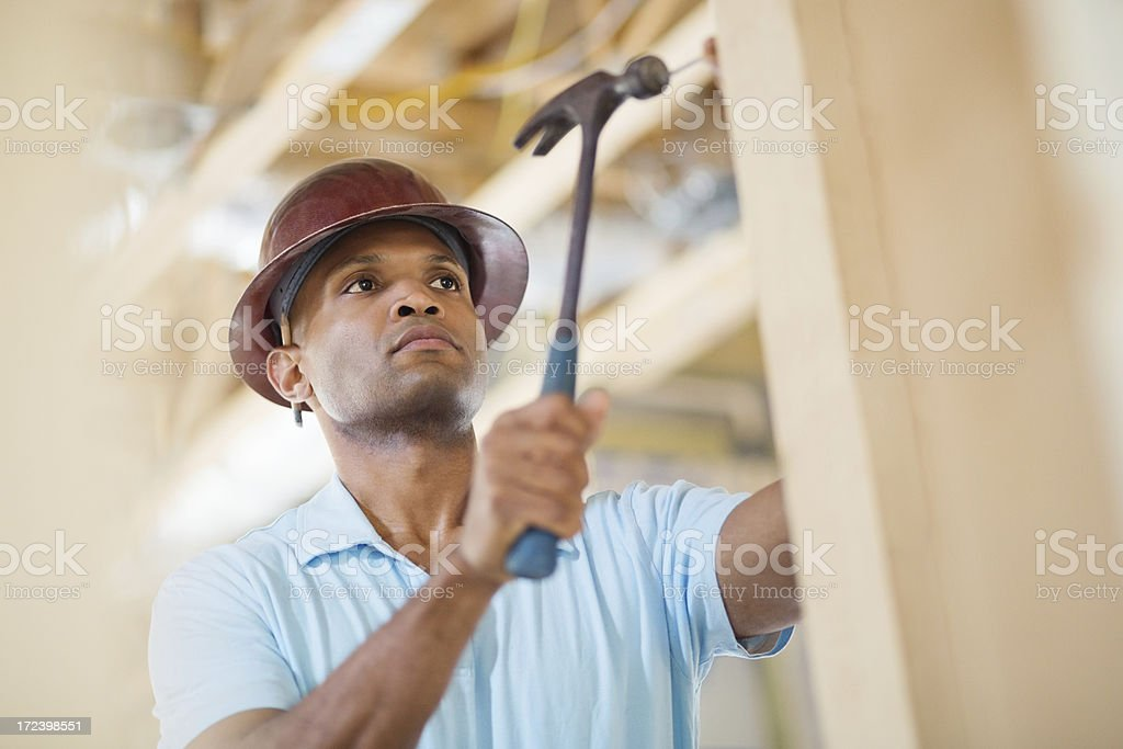 Male Construction Worker Hammering Nail Into Wood At Site royalty-free stock photo