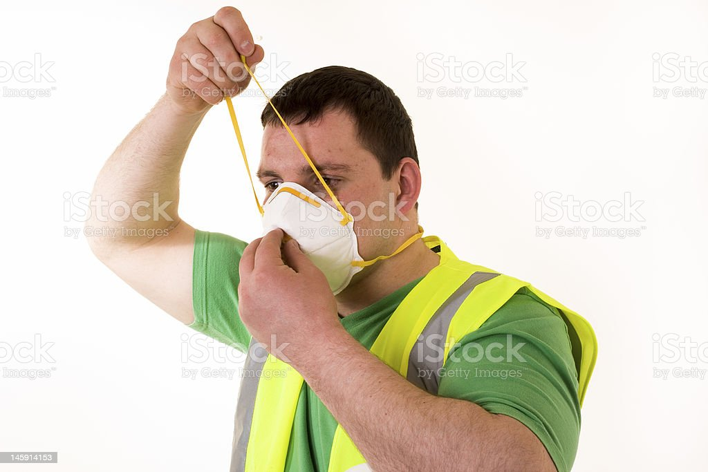 Male construction worker putting on a dust mask stock photo