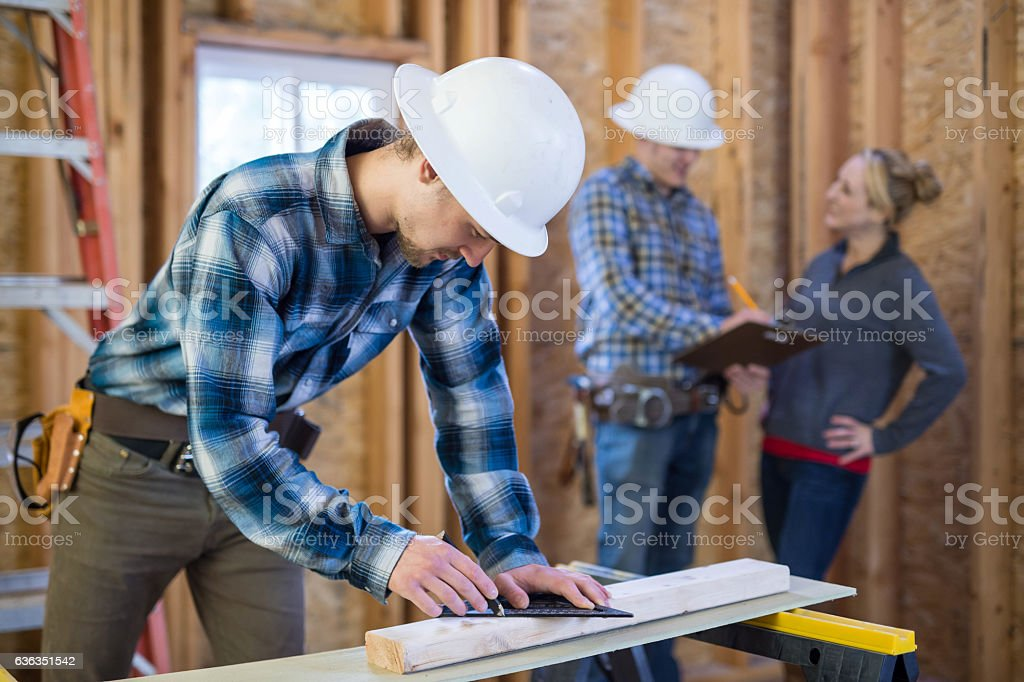 Male construction worker using a square and pencil stock photo
