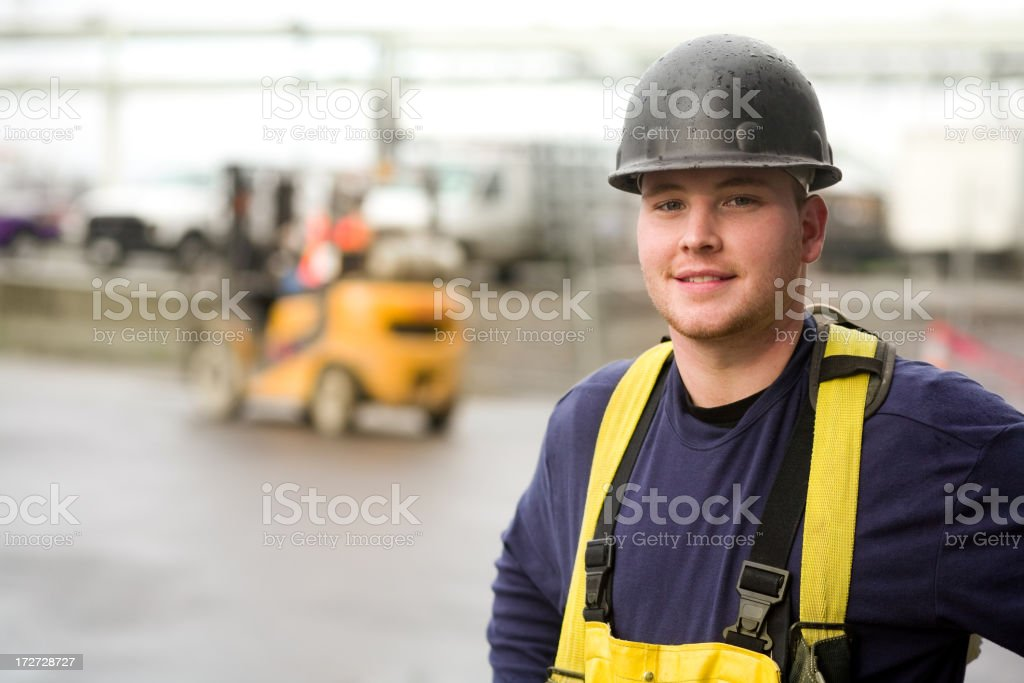 Male construction worker wearing black hard hat and overalls royalty-free stock photo
