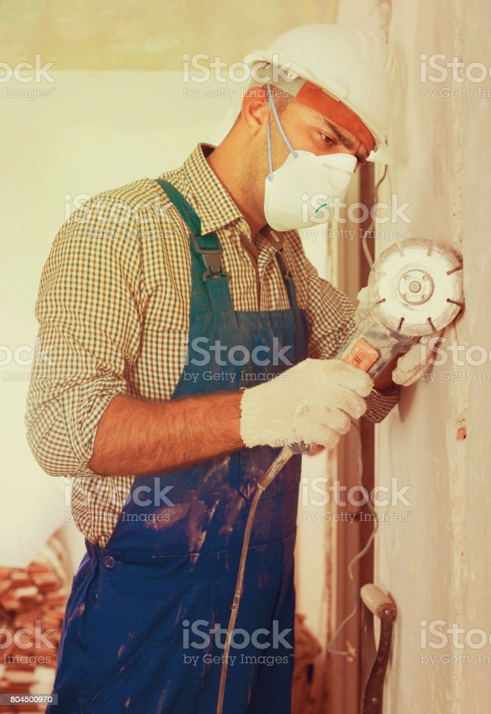Male constructor repairing with drill in mask stock photo