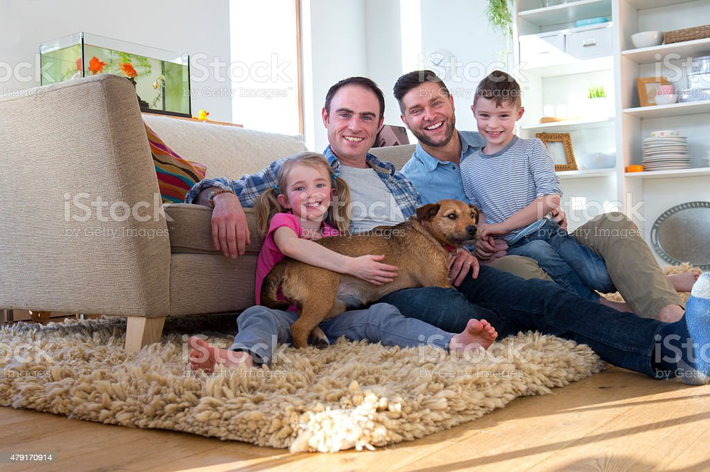 Male couple posing with son, daughter and dog stock photo