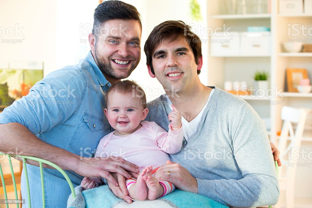 Male couple posing with their daughter at home stock photo