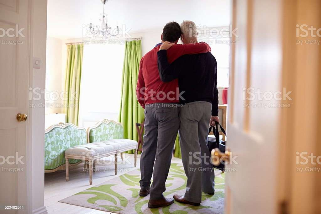 Male couple with arms around each other arrive in stock photo