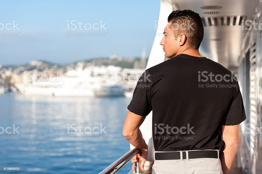 Male crew member looking from yacht boat stock photo