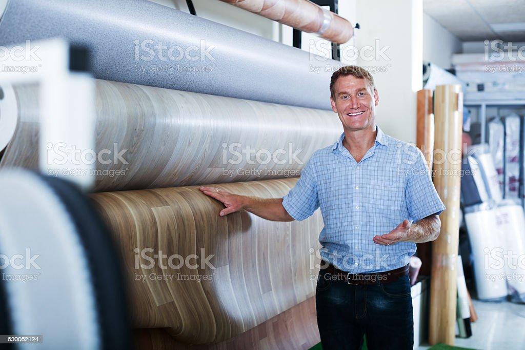 male customer choosing linoleum flooring stock photo