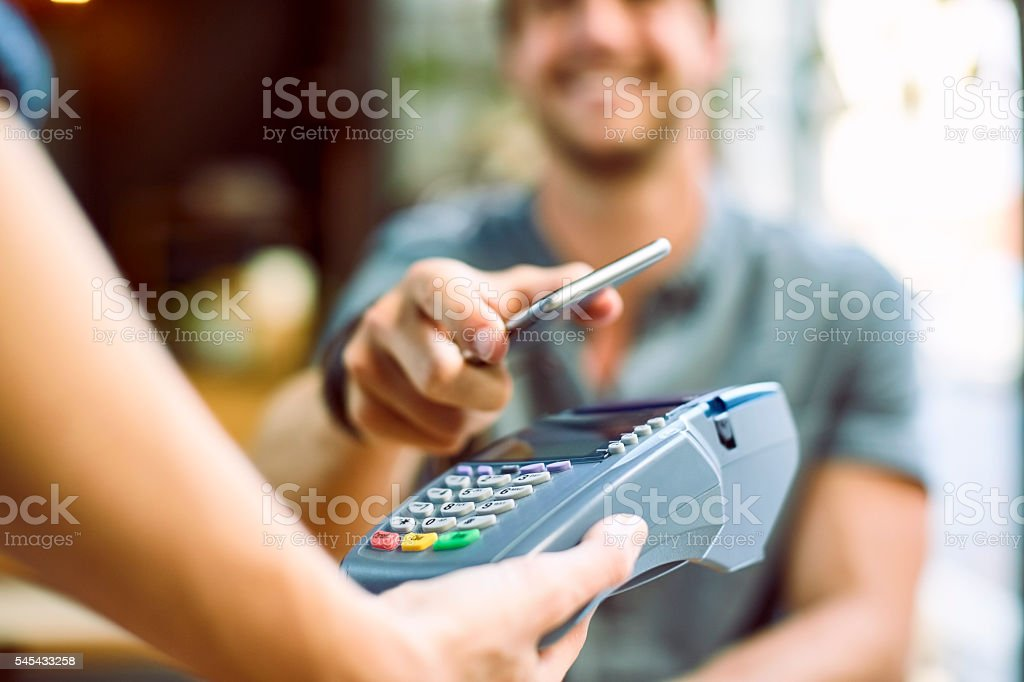 Male customer making mobile payment at cafe stock photo