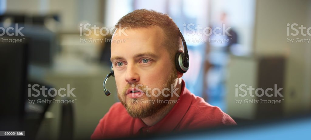 a young male customer services representative on the phone to a...