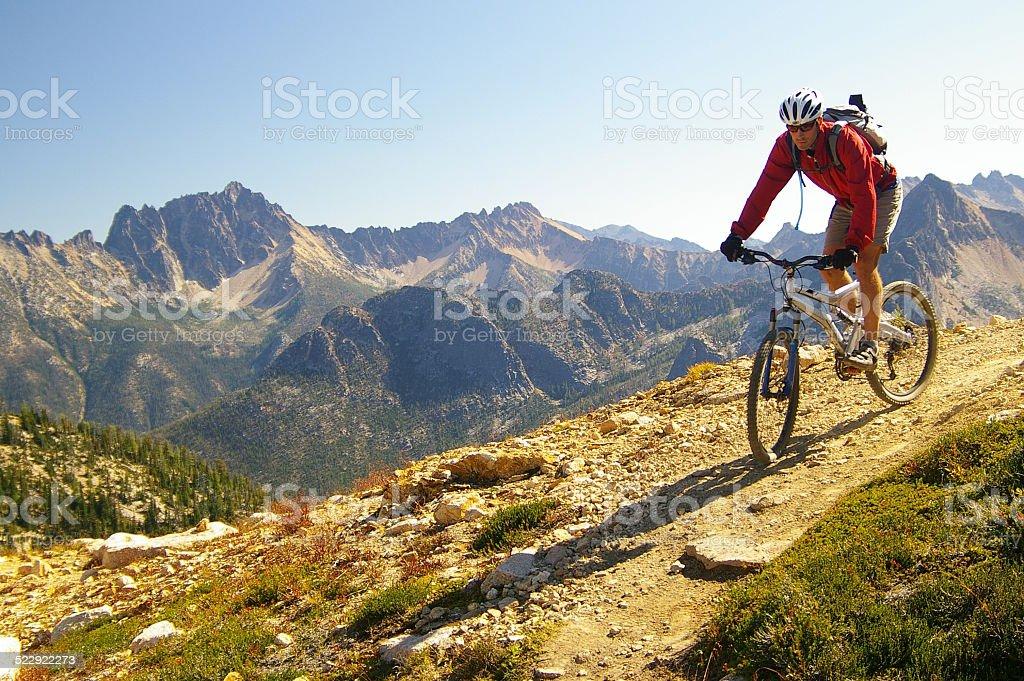 Male Cyclist riding mountain bike high mountains stock photo