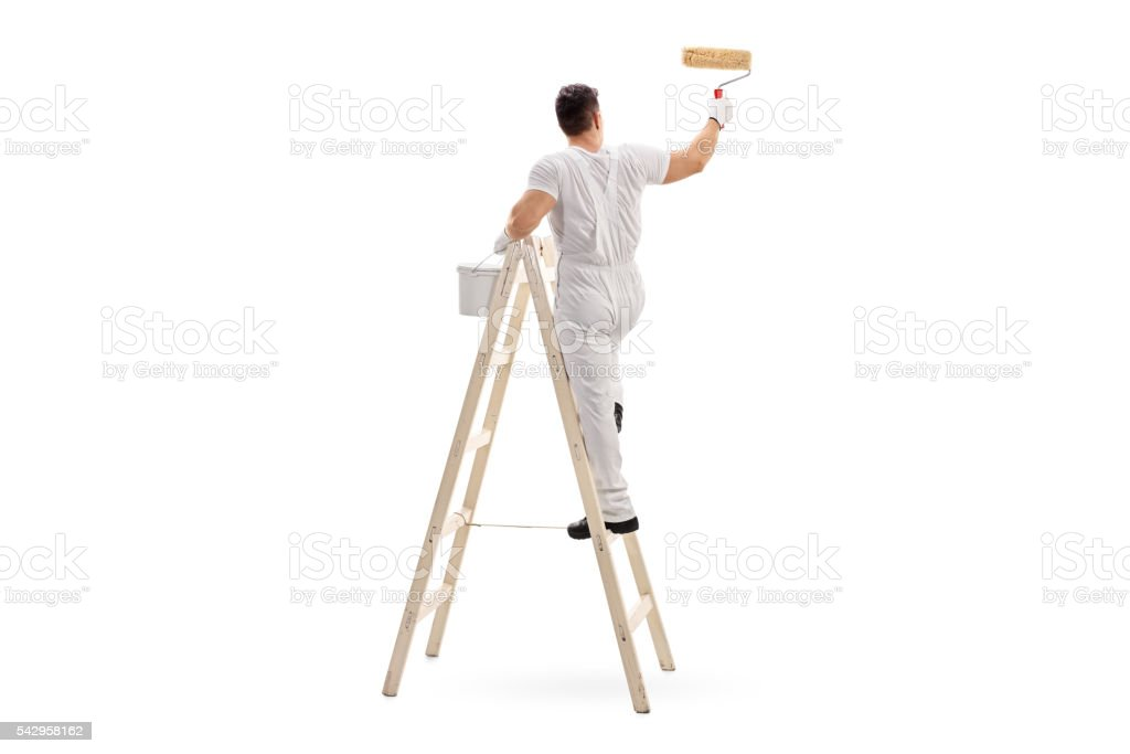 Male decorator painting with a roller stock photo