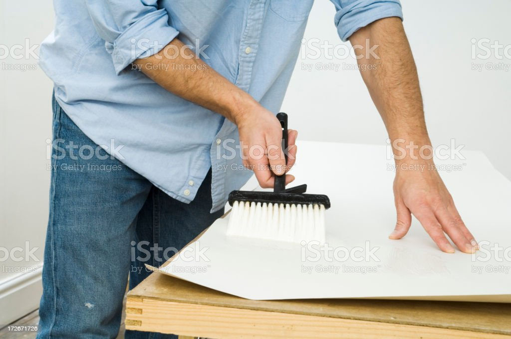 Male decorator pasting a sheet of wallpaper royalty-free stock photo